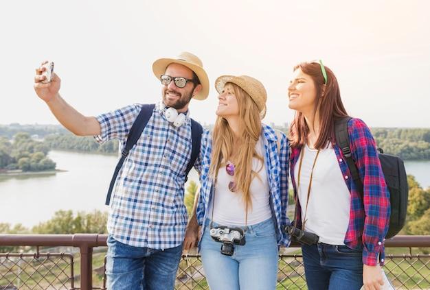 Группа счастливых друзей, берущих себя на мобильный телефон на открытом воздухе