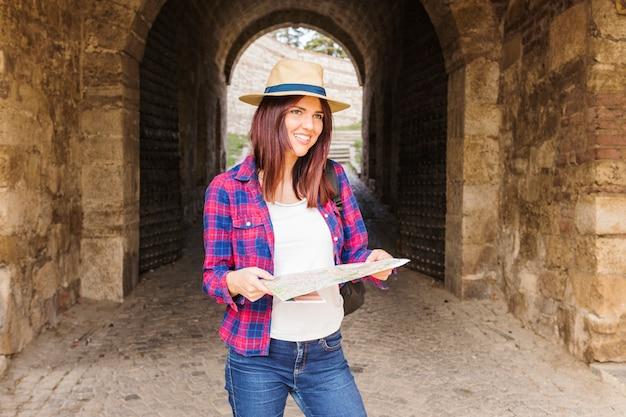 地図を保持している笑顔の若い女性の肖像