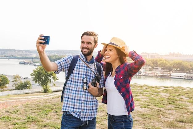 屋外で携帯電話でセルフをする若いカップルに笑顔