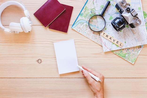 木製の背景に旅行者のアクセサリーと紙に書いている人