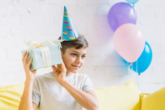 誕生日プレゼントを揺する少年のクローズアップ