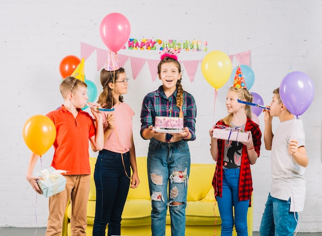 誕生日ケーキを持っている女の子を見ている友人のグループ