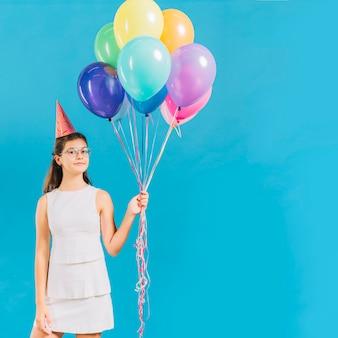 青い背景にカラフルな風船を持っている少女の肖像