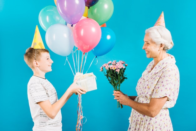 青い背景で幸せな祖母に誕生日の贈り物を与える少年