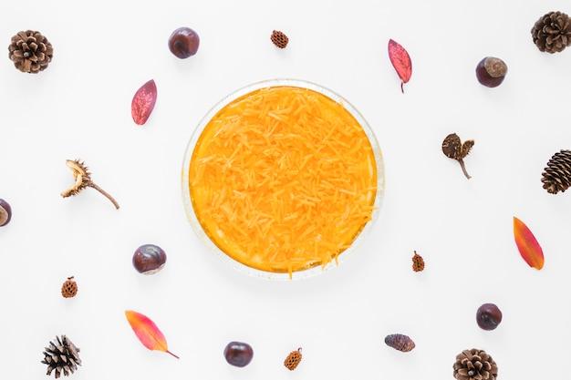 Морковь в тарелке между корягами и листвой