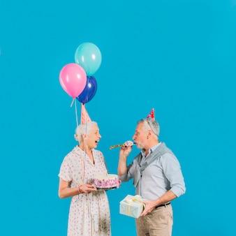 青い背景に誕生日のケーキを抱いている彼の妻の間にパーティーホーンを吹く男