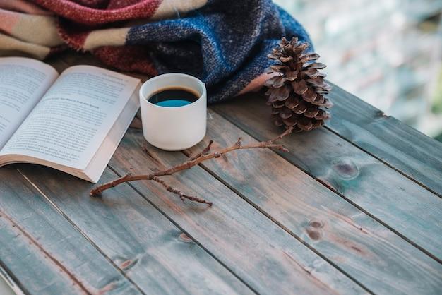 テーブルの上のカップの近くの本