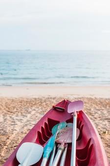 砂浜の海岸にある赤いカヤック
