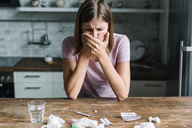 Молодая женщина, страдающая от тошноты с лекарствами и стаканом воды на столе