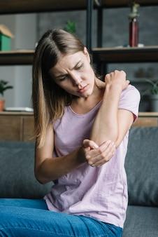 彼女の肘に触れる病気の若い女性の肖像