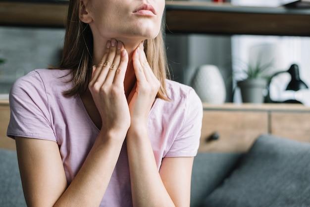 喉、痛みに苦しむ女性のクローズアップ