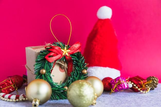 サンタの帽子と小さな花輪のクリスマスの組成