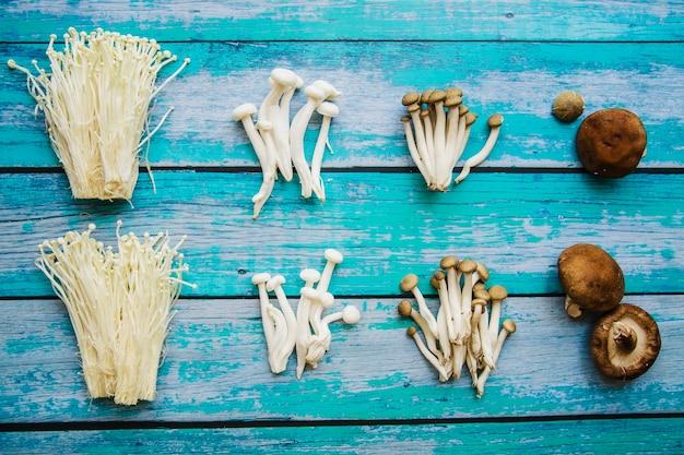 Различные виды сырых здоровых грибов, расположенных над старым деревянным столом
