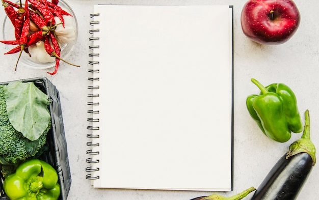 白い背景に空の日記と新鮮な野菜