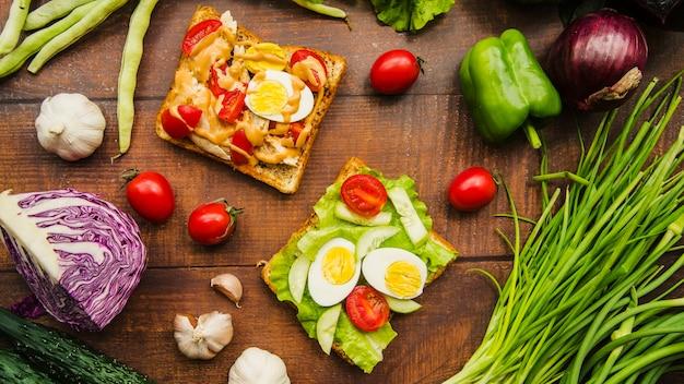 木製のテーブル上に異なる健康的な野菜を持つおいしい肉のサンドイッチ