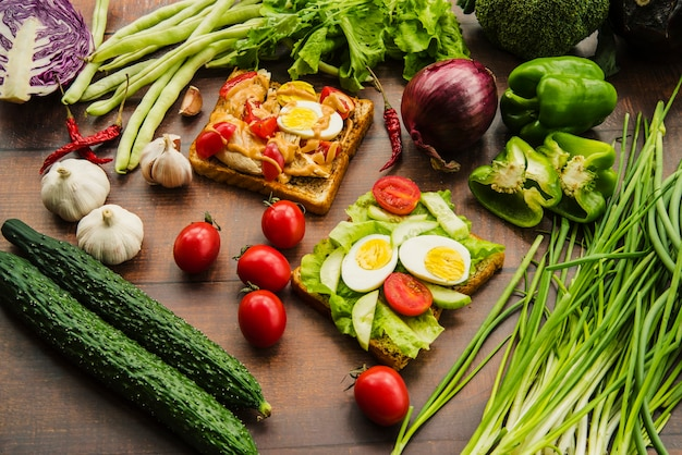 木製のテーブルにさまざまな健康的な野菜とおいしいサンドイッチ