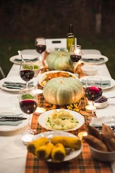 Праздничный стол с различными продуктами питания и тыквами