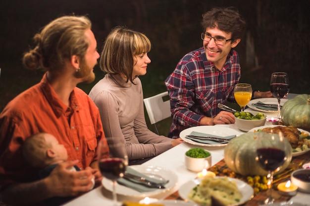 食べ物と一緒にテーブルに座る人々
