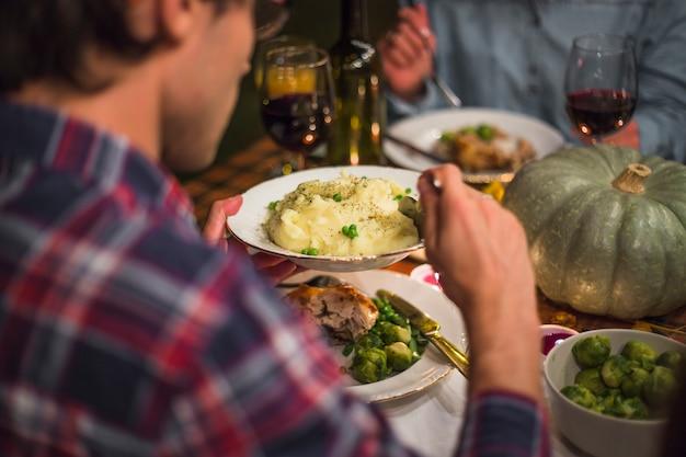 食卓でテーブルに人を保持している男