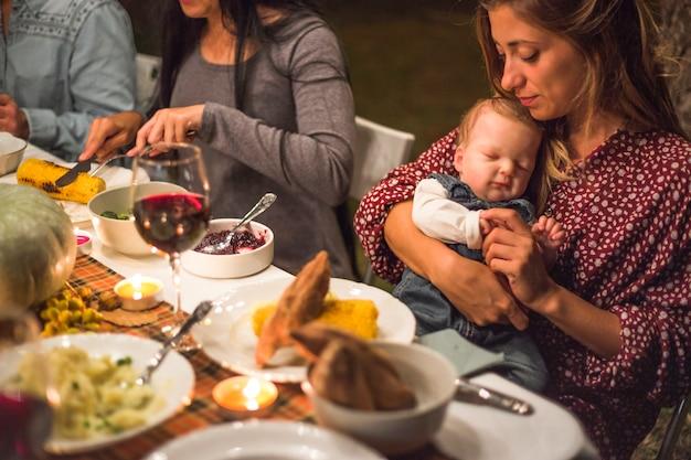 家族の夕食時に小さな赤ちゃんを持つ母親