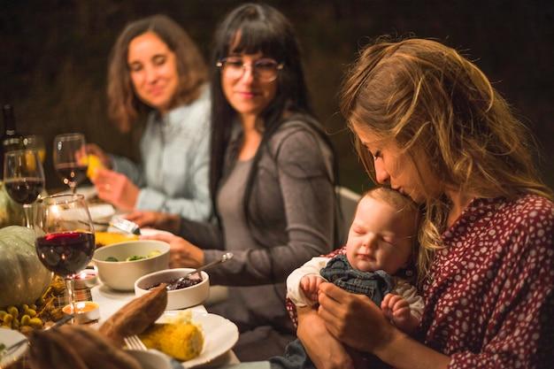 家族の夕食に小さな赤ちゃんにキスする母