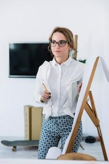 Молодой предприниматель, холдинг карандаш, объясняя новый бизнес-план