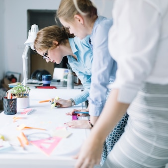Ряд бизнес-леди рисунок проекта на белой бумаге на рабочем месте