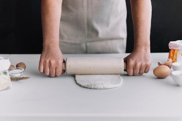 キッチン、カウンターにローリングピンで生地を平らにする人の手のクローズアップ