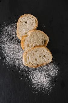 黒の背景に新鮮なパンと小麦粉のスライス