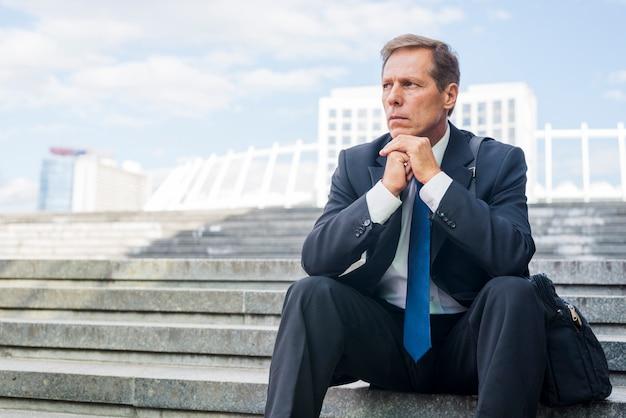 深刻な成熟したビジネスマン、階段に座っている