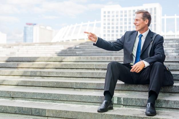 階段に座っている間に何かを指している笑顔の成熟したビジネスマン