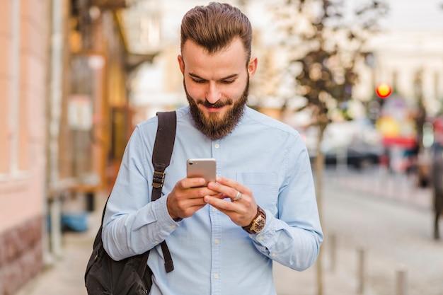 携帯電話を使用している若い男のクローズアップ