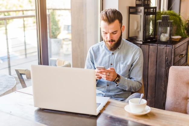 Молодой человек с помощью мобильного телефона с ноутбуком и чашкой кофе на столе