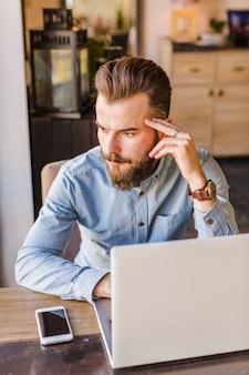 デスクにノートパソコンと携帯電話を置いてレストランに座っているひげのある若い男