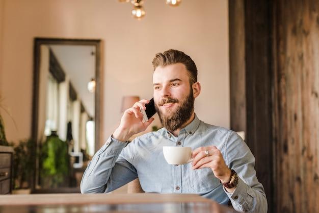 コーヒーを飲みながら携帯電話で話す男