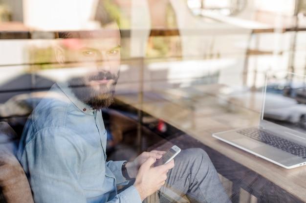 カフェで透明なガラスを通して見た携帯電話で若い男