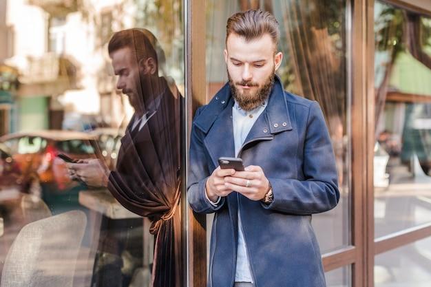 Бородатый молодой человек, опираясь на стекло окна с помощью мобильного телефона