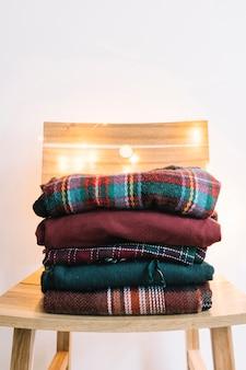 木製の椅子の冬のセーターの山