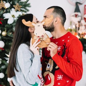 おもちゃの鹿の後ろにキスをするカップル