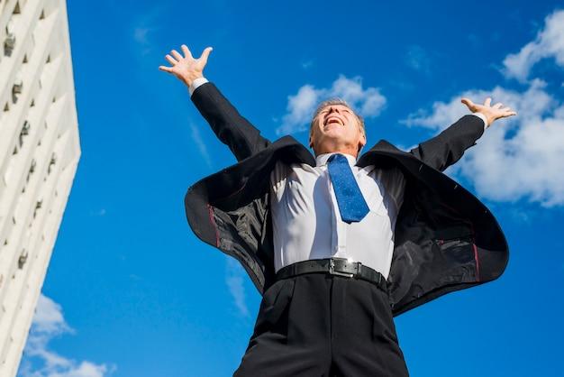 Возбужденный бизнесмен поднимает руки против неба.