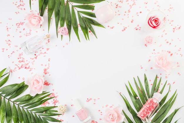 Повышенный вид гималайской соли; листья; лак для ногтей; бутылка; увлажняющий крем и цветы на белом фоне