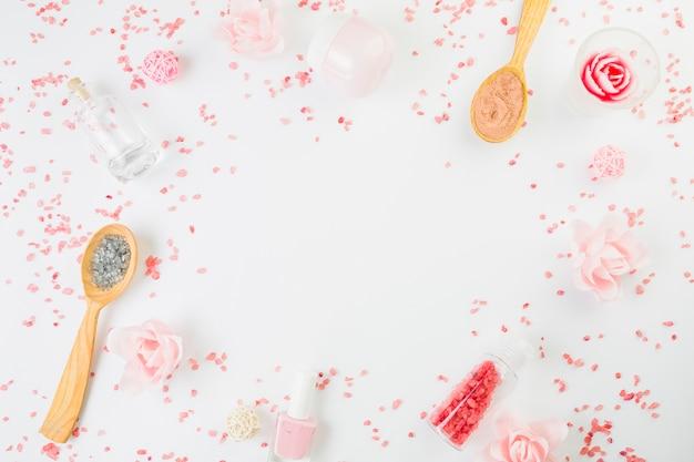 Повышенный вид косметических продуктов, образующих круглую рамку на белой поверхности