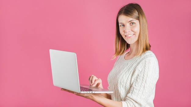 ピンクの背景にラップトップを使用して笑顔の若い女性の肖像画