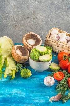 青色の木製の表面に新鮮な有機野菜のクローズアップ