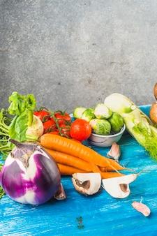 青い木製の表面に様々な新鮮な有機野菜