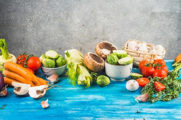 青色の有機卓上に新鮮な有機野菜