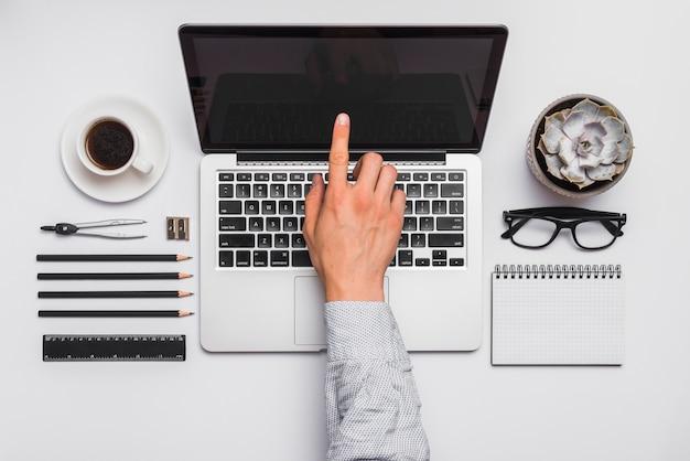 Указательный палец человека, касаясь экрана ноутбука в офисе