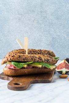 キッチンカウンター上の木製のうどんの上に、イチジクのスライスとアーモンドのあるおいしいホットドッグのクローズアップ