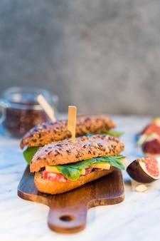 イチジク、アーモンドの近くの木製のチョッピングボード上のおいしいホットドッグのクローズアップ