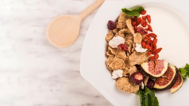 白い背景の上に木製の取鍋の近くのプレートで健康的な朝食の高い角度のビュー
